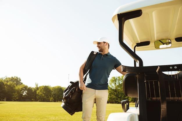 Młody człowiek stojący z torbą golfową
