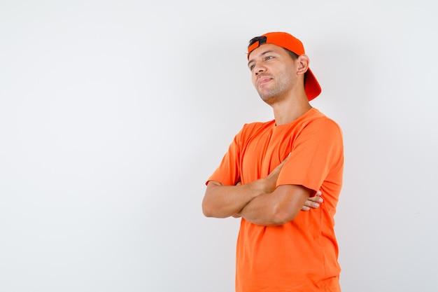 Młody człowiek stojący ze skrzyżowanymi rękami w pomarańczowej koszulce i czapce i wyglądający marzycielsko