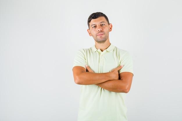Młody człowiek stojący ze skrzyżowanymi rękami w t-shirt i patrząc pewnie