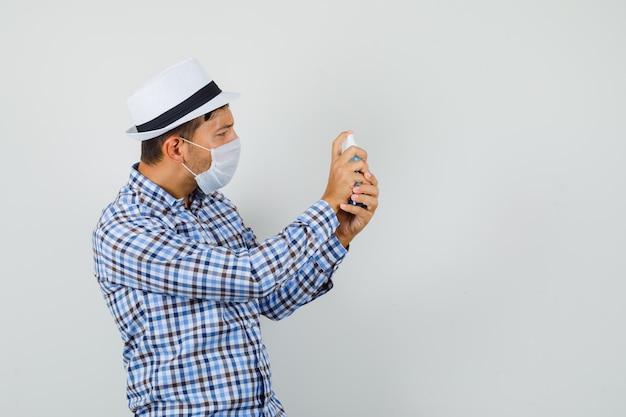 Młody człowiek stosując spray dezynfekujący w kraciastej koszuli