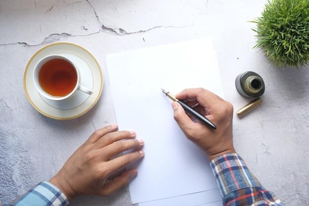 Młody człowiek strony pisania piórem na papierze na stole
