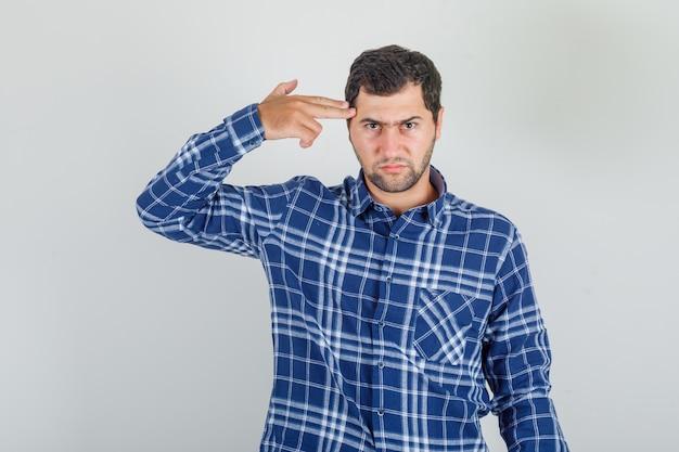 Młody człowiek strzelający z pistoletu ręcznego w kraciastej koszuli i wyglądający na przygnębionego.