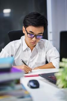 Młody człowiek studiuje i pisze na notebooka z laptopa