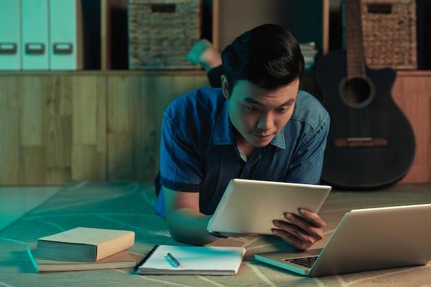 Młody człowiek studiuje na jutrzejsze zajęcia