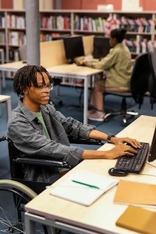 Młody człowiek studiuje w bibliotece uniwersyteckiej