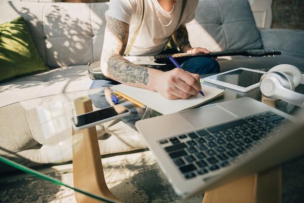 Młody człowiek studiuje w domu podczas kursów online lub samodzielnie otrzymuje bezpłatne informacje
