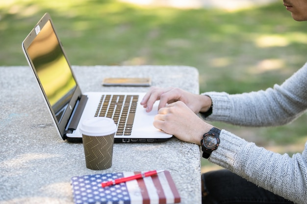 Młody człowiek studiuje z komputerem podczas słuchania muzyki w słuchawkach w parku bez maski