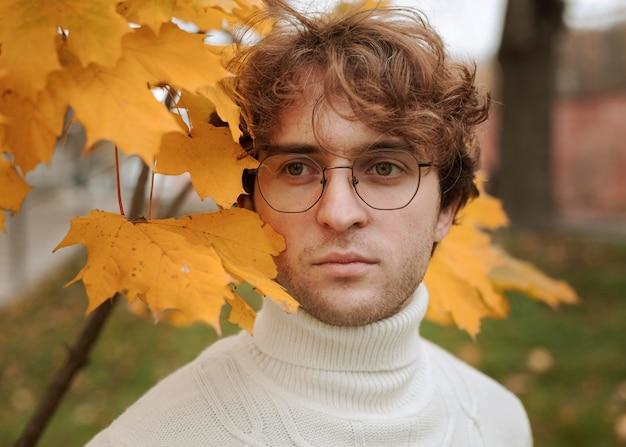 Młody człowiek stwarzających w jesiennych liściach
