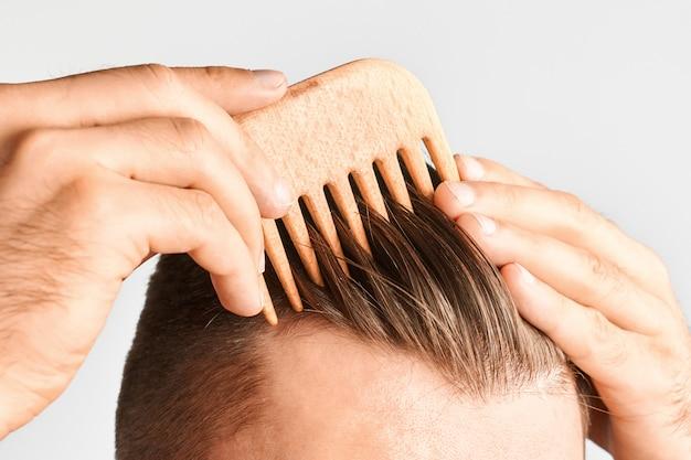 Młody człowiek stylizuje włosy drewnianym grzebieniem. stylizacja włosów w domu. reklamowa koncepcja szamponu dla zdrowych włosów i przeciw łupieżowi.