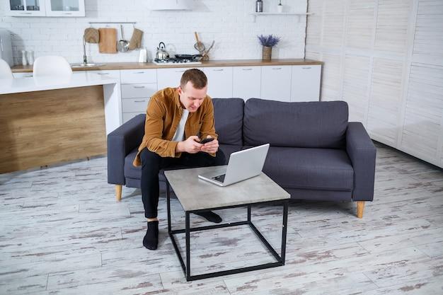Młody człowiek sukcesu siedzi w domu na kanapie z laptopem i pracuje. praca zdalna podczas kwarantanny.