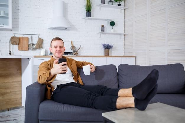 Młody człowiek sukcesu siedzi w domu na kanapie z telefonem i rozmawia przez łącze wideo. praca zdalna podczas kwarantanny.