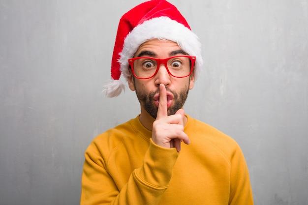 Młody człowiek świętuje boże narodzenie trzymania prezentów, utrzymując w tajemnicy lub prosząc o ciszę