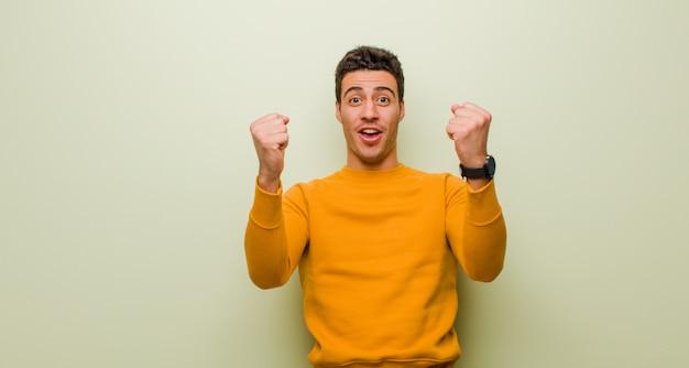 Młody człowiek świętuje niesamowity sukces jak zwycięzca, wyglądając na podekscytowanego i radosnego mówiąc: weź to! nad ścianą