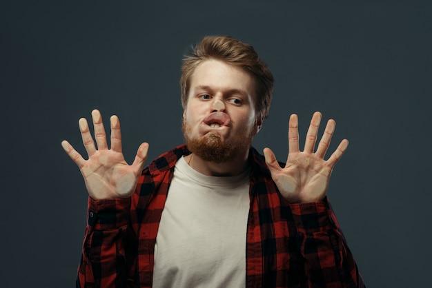 Młody człowiek szalona twarz i ręce zmiażdżone na przezroczystym szkle.