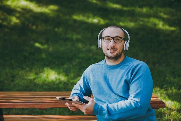 Młody człowiek szczęśliwy, biznesmen lub student w okularach dorywczo niebieska koszula siedzi przy stole ze słuchawkami, komputer typu tablet w parku miejskim, słuchanie muzyki, odpoczynek na świeżym powietrzu na zieloną przyrodę. koncepcja wypoczynku stylu życia.