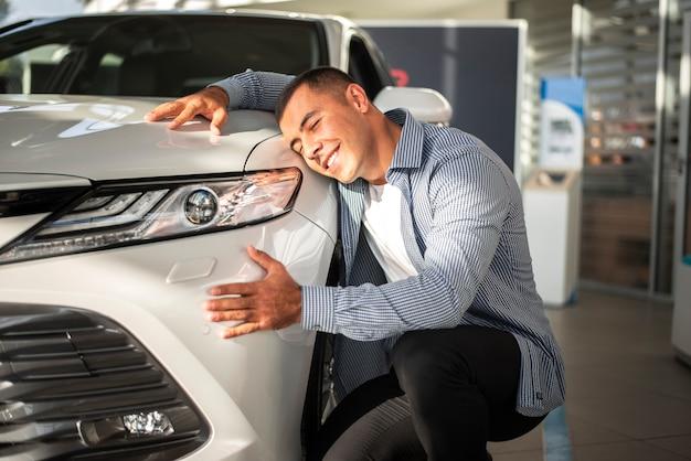 Młody człowiek szczęśliwy dla swojego nowego samochodu