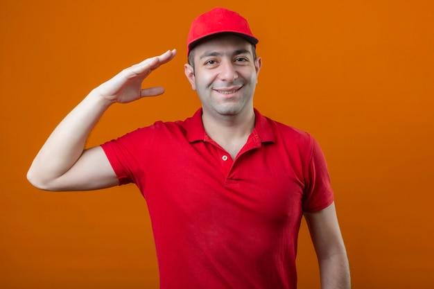 Młody człowiek szczęśliwy dostawy w czerwonej koszulce polo i czapce, dzięki czemu salutować gotowy do pracy uśmiechnięty przyjazny na pojedyncze pomarańczowe tło