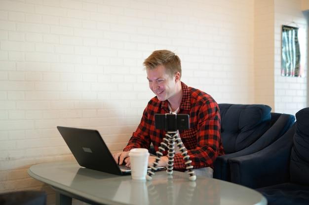 Młody człowiek szczęśliwy hipster za pomocą laptopa podczas vlogowania w kawiarni