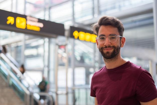 Młody człowiek szczęśliwy i śmiejąc się na lotnisku