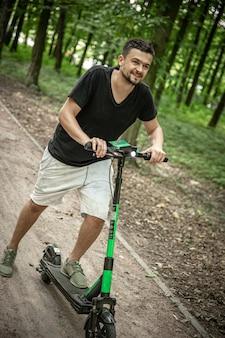 Młody człowiek szczęśliwy, jazda na skuterze elektrycznym, koncepcja ekologicznego transportu.
