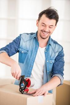 Młody człowiek szczęśliwy opakowania pudełka.