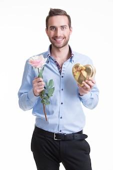 Młody człowiek szczęśliwy z różową różą i prezentem - na białym tle.