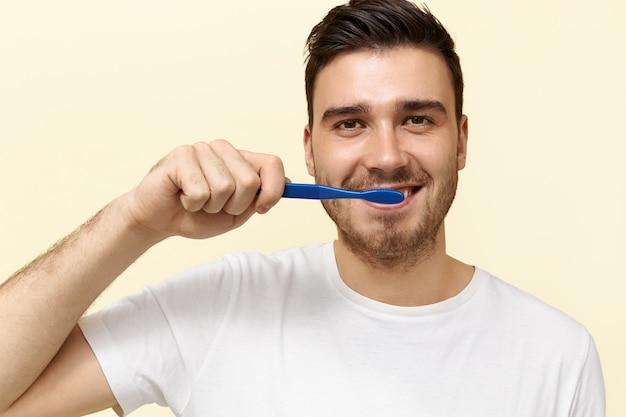 Młody człowiek szczotkuje zęby