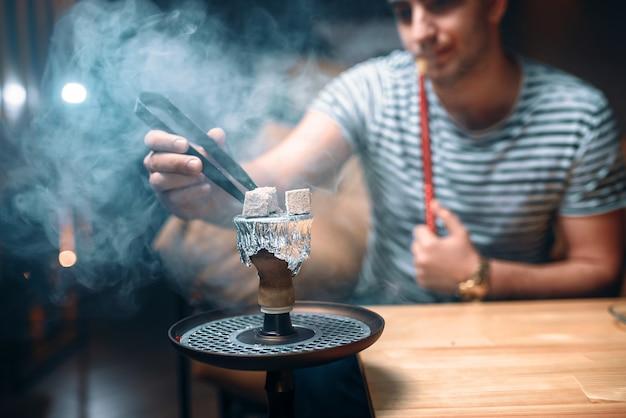 Młody człowiek szczypcami rozpala węgiel w barze fajki wodnej