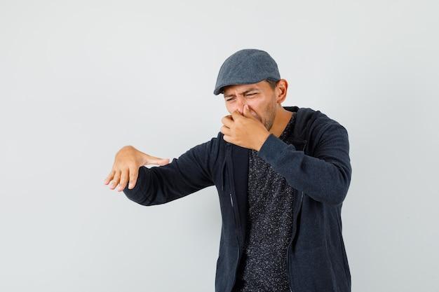 Młody człowiek szczypie nos z powodu nieprzyjemnego zapachu w koszulce, kurtce, czapce i wygląda na zniesmaczonego, widok z przodu.