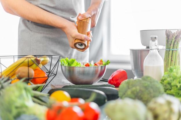 Młody człowiek szef kuchni gotuje zdrowej sałatki