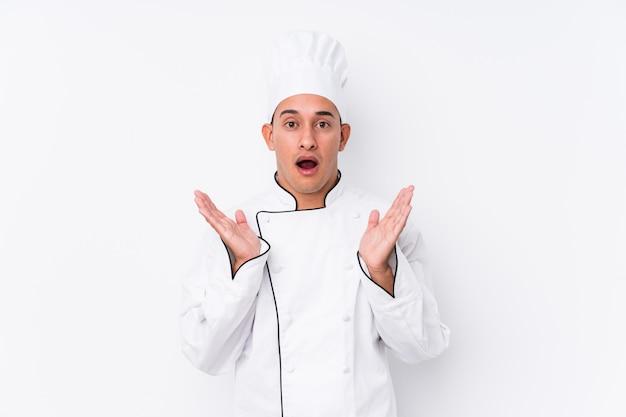 Młody człowiek szef kuchni łacińskiej zaskoczony i zszokowany.