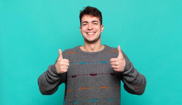 Młody człowiek szeroko uśmiechnięty, szczęśliwy, pozytywny, pewny siebie i odnoszący sukcesy, z dwoma kciukami do góry