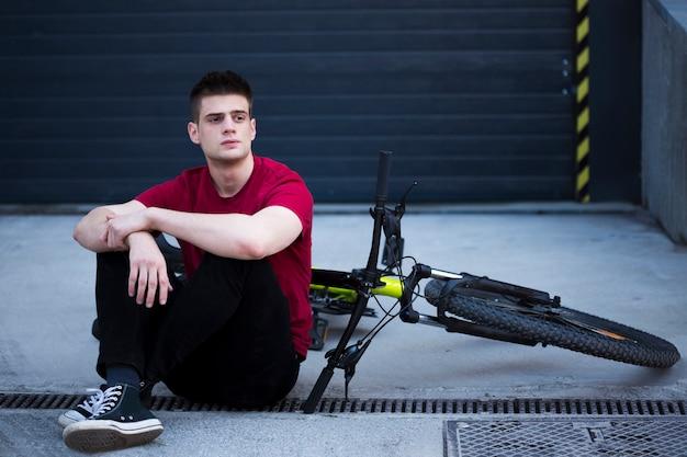 Młody człowiek szuka daleko i siedzi obok roweru