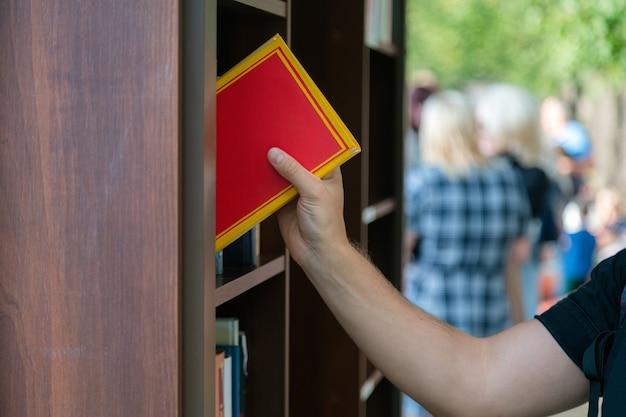 Młody człowiek szuka książki w księgarni. student uniwersytetu.