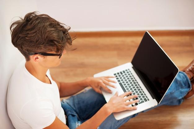 Młody człowiek szuka miło i za pomocą laptopa