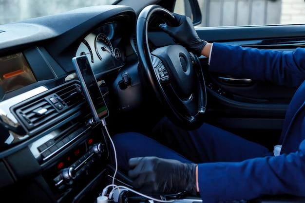Młody człowiek taksówkarz z rękawiczkami siedzi na siedzeniu kierowcy w samochodzie