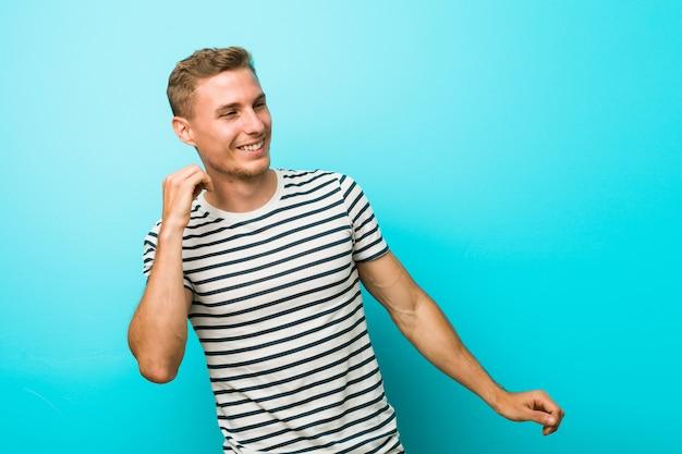 Młody człowiek tańczy i zabawy na tle niebieskiej ściany