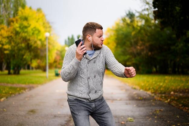 Młody człowiek tanczy na alei w parku z słuchawkami