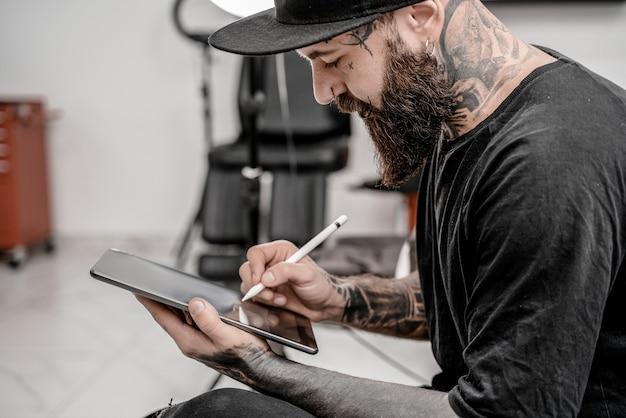 Młody człowiek tatuażysta z brodą, trzymając ołówek i szkic, patrząc pozytywnie i szczęśliwie stojąc i uśmiechając się w miejscu warsztatu.