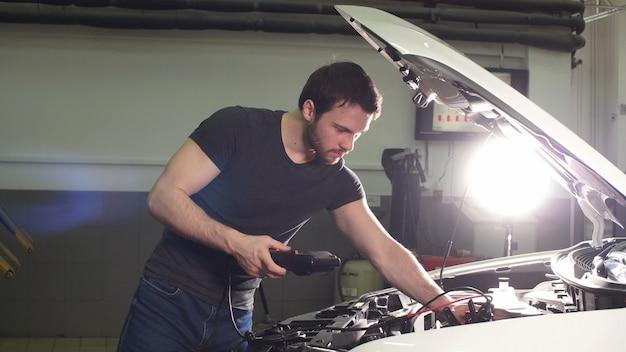 Młody człowiek technik robi silnik serwis samochodu w garażu.