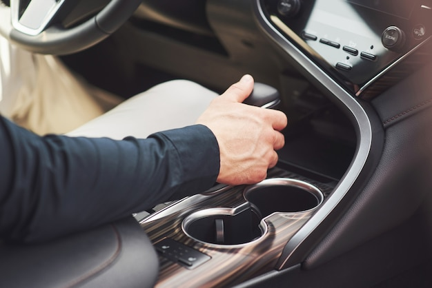 Młody człowiek to mężczyzna za kierownicą nadrzewnego samochodu.