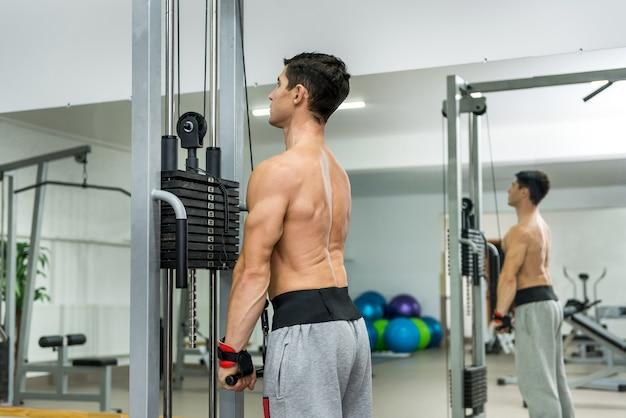 Młody człowiek, trening w sprzęt sportowy w siłowni