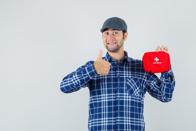 Młody człowiek trzyma apteczkę, pokazując kciuk w koszulę, czapkę i wyglądający wesoło, widok z przodu.