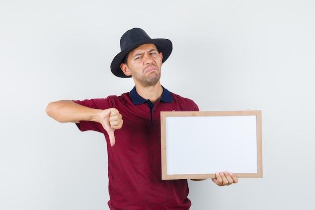 Młody człowiek trzyma białą deskę z kciukiem w dół w t-shirt, kapelusz i patrząc niezadowolony. przedni widok.