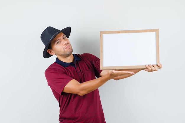 Młody człowiek trzyma białą tablicę w t-shirt, kapelusz, widok z przodu.