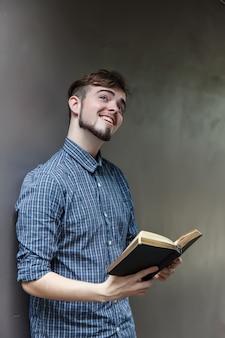 Młody człowiek trzyma biblię, uczeń z książką