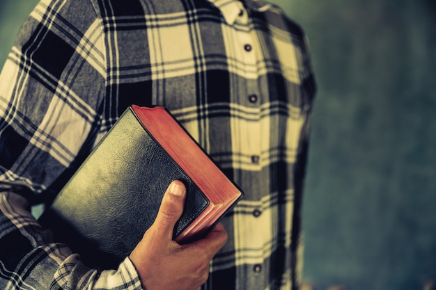 Młody człowiek trzyma biblię w jego rękach