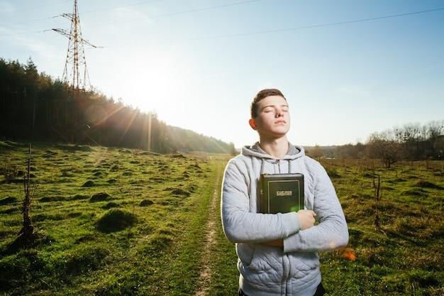Młody człowiek trzyma biblię w parku