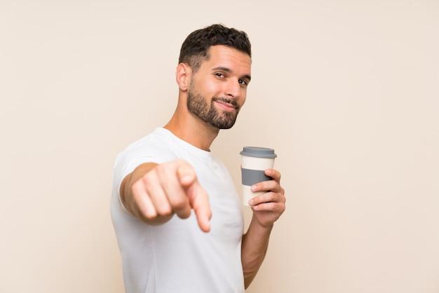 Młody człowiek trzyma bierze oddaloną kawę nad odosobnionym tłem