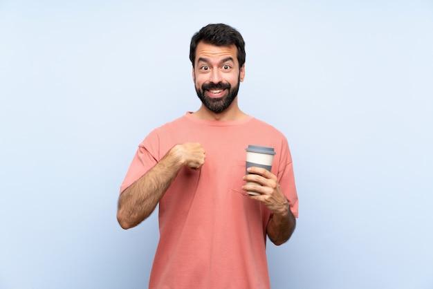 Młody człowiek trzyma brodą kawę nad odosobnioną błękit ścianą z niespodzianka wyrazem twarzy z brodą